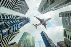 Högväxta stadsbyggnader och plant ett flyg som är över huvudet i morgon Royaltyfri Bild