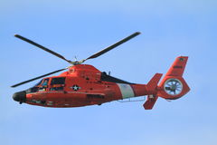 HH 65 Dolphin US Coast Guard Helicopter. HONOLULU - JAN. 17 2014 U.S. COAST GUARD Helicopter flies over Waikiki Beach during a routine run along the bea HONOLULU Royalty Free Stock Image