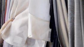 Hhands de la costurera busca las muestras de la tela para las cortinas de costura metrajes