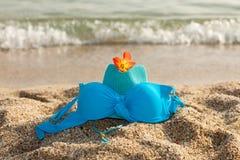 Hhat, bikini en bloem op het strand Stock Afbeelding