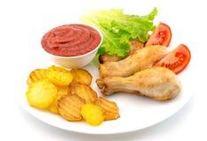 Hühnerbeine auf einer weißen Platte mit Scheiben der Tomate und des Kopfsalates und der Pommes-Frites und des Ketschups auf weiße Stockbild
