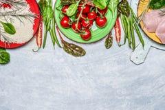 Hühnerbrust mit Reis, frischem köstlichem Gemüse und Bestandteilen für das geschmackvolle Kochen auf rustikalem hölzernem Hinterg Stockfoto