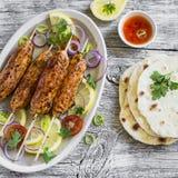 Hühnerkebabs auf hölzernen Aufsteckspindeln auf einer ovalen Platte und einer selbst gemachten Tortilla Lizenzfreie Stockfotos