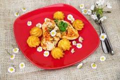 Hühnersteak, gebratener Kartoffelkorb und Frühlings-Saison-Blumen Stockfotos