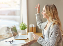 Hi. Beautiful young woman working with computer, holding a cup of drink and waving in the window. Royalty Free Stock Image