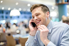 Hi buddy, i am in restaurant. Young male executive talking on mobile in a cafe royalty free stock photos
