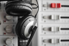 Hi-fi sound guard and noise reduction headphones over digital sound mixer. Hi-fi sound guard and noise reduction headphones over blured digital portable  sound Royalty Free Stock Photos