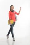 Hi guys! Happy teenage schoolgirl greeting someone while standin Royalty Free Stock Photography