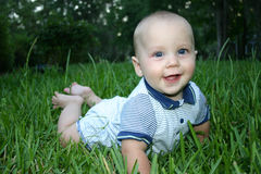 Hi Mom!. Baby beginning to crawl in grass Stock Images
