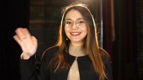 Hi, my friend. Portrait of young woman in black raising hand and waving in greeting gesture, welcoming familiar person