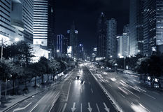 Hi-rise building and vehicles commute at night time Royalty Free Stock Photo