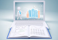 Hi-tech building in laptop screen and open book Stock Photo
