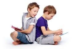 Hi-tech kids. Boys sitting back to back using hi-tech digital pads Royalty Free Stock Image