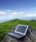 Hi-tech and nature. Laptop lying on the stone against mountain scenery Royalty Free Stock Photo