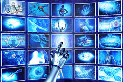 Hi-tech screens. Robot arm pointing at hi-tech screens Stock Photo