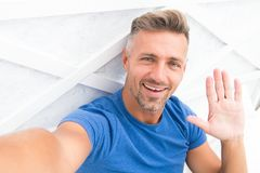 Hi there. Man taking selfie photo smartphone waving hand. Streaming online video. Mobile internet. Shooting for blog. Mature man blogger. Blog online content royalty free stock images