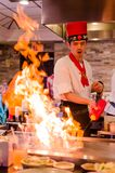 Hibachi restaurant chef preparing meal and entertaining guests. Asian japanese hibachi cook makes meal while guests have fun watching his antics and moves Stock Photo