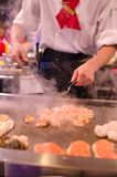 Hibachi restaurant chef preparing meal and entertaining guests. Asian japanese hibachi cook makes meal while guests have fun watching his antics and moves Stock Photography