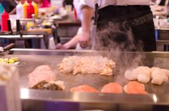 Hibachi restaurant chef preparing meal and entertaining guests. Asian japanese hibachi cook makes meal while guests have fun watching his antics and moves Stock Images
