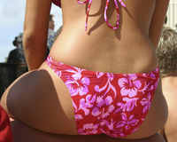 Hibiscus Bikini. Sexy woman in pink floral bikini sitting on man's shoulders at concert event Royalty Free Stock Photos