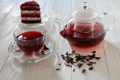 Hibiscus tea in cup and teapot, tea leaves, piece of red velvet cake on white wooden background. stock images