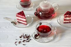 Hibiscus tea in cups and teapot, tea leaves, for dessert red velvet cake pieces on white wooden background. royalty free stock photo