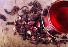 Hibiscus tea in a glass cup on a wooden table among the rose petals and dry tea. Vitamin tea for cold and flu Stock Photography