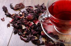 Hibiscus tea in a glass cup on a wooden table among the rose petals and dry tea. Vitamin tea for cold and flu Royalty Free Stock Photography