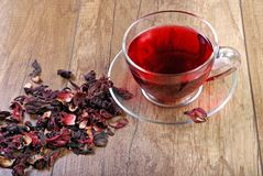 Hibiscus tea in a glass cup on a wooden table among the rose petals and dry tea. Vitamin tea for cold and flu Royalty Free Stock Image