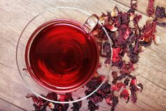 Hibiscus tea in a glass cup on a wooden table among the rose petals and dry tea. Vitamin tea for cold and flu Stock Photos