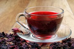 Hibiscus tea in a glass cup on a wooden table among the rose petals and dry tea. Vitamin tea for cold and flu Stock Image