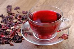 Hibiscus tea in a glass cup on a wooden table among the rose petals and dry tea. Vitamin tea for cold and flu Royalty Free Stock Photos