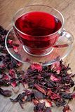 Hibiscus tea in a glass cup on a wooden table among the rose petals and dry tea. Vitamin tea for cold and flu Stock Images