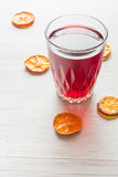Hibiscus tea in a glass mug on a wooden table among rose petals and dry tea custard Royalty Free Stock Photography
