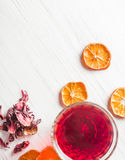 Hibiscus tea in a glass mug on a wooden table among rose petals and dry tea custard Royalty Free Stock Photo