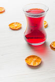 Hibiscus tea in a glass mug on a wooden table among rose petals and dry tea custard Stock Photo