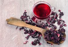 Hibiscusthee in een glaskop op een houten lijst onder de roze bloemblaadjes en de droge thee Vitaminethee voor koude en griep Exe stock afbeeldingen