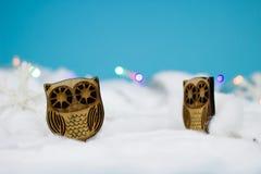 Hiboux en bois dans la neige Photos libres de droits
