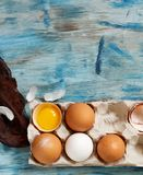 Сhicken eggs in a box. On  a blue wooden background Stock Image