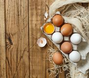 Сhicken eggs in a box. On a wooden background Royalty Free Stock Photo