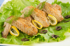 Сhicken wings. Fried chicken wings with lemon and lettuce Stock Photography