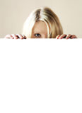 Hidden. A blond young woman is hidden behind a table Royalty Free Stock Image