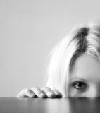 Hidden. A blond young woman is hidden behind a table stock photography