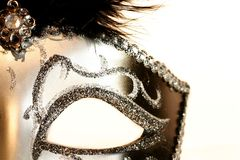 Hidden. Half of a black and silver mask on a white background Royalty Free Stock Photo
