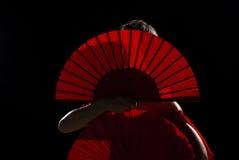 Hidden. Female flamenco performer hidden behind her folding fans royalty free stock image