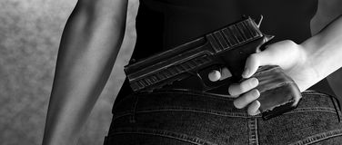 Hit man. Woman holding a gun behind her back Stock Photography