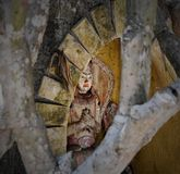 Hidden balinese spiritual wooden statue in a niche. Hidden balinese spiritual wooden statue with praying hands in a niche Royalty Free Stock Photo