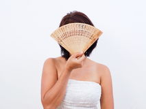 Woman hides behind hand fan Stock Photos