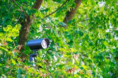 Hidden black metal street security video camera with back light and cobweb on bracket in green bushes stock images