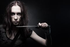 Hidden blade. Pretty soldier with dagger posing over dark background royalty free stock image